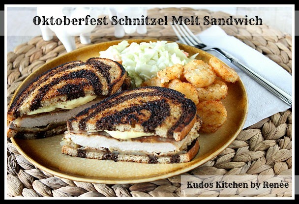 Breaded pork schnitzel sandwich with Swiss cheese on marbled rye bread.