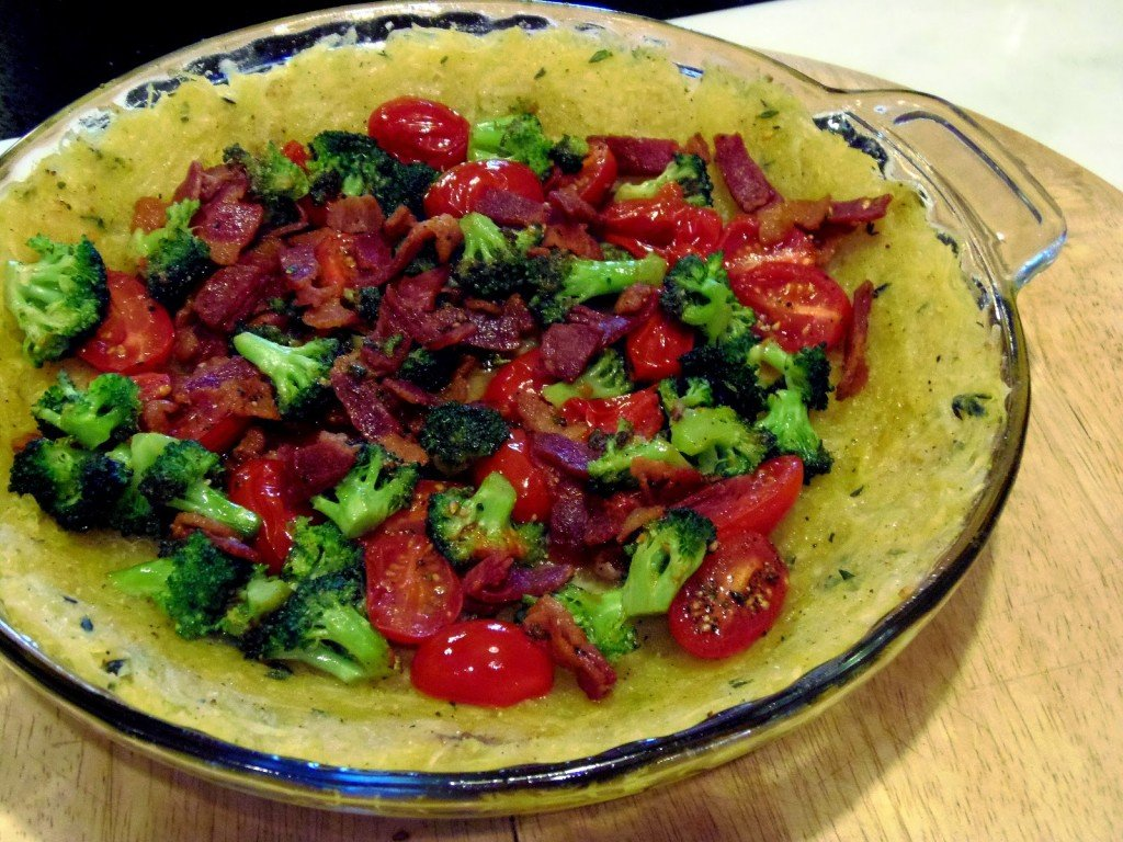 """Roasted spaghetti squash is pressed into a pie plate and baked. The """"crust"""" is then filled with veggies, eggs and cheese and baked again."""