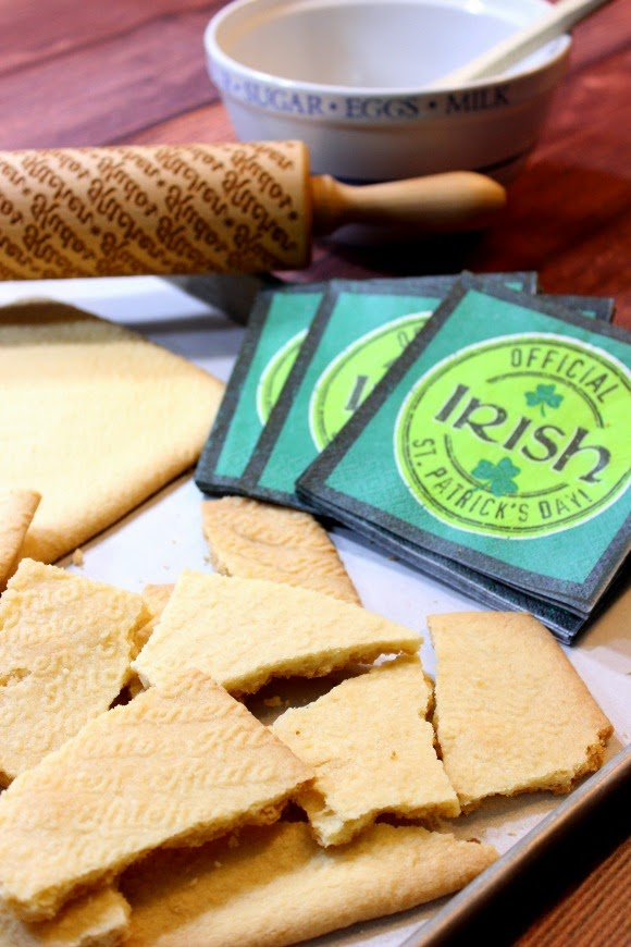 Irish shortbread cookie pieces on a baking tray with a rolling pin and green napkins.