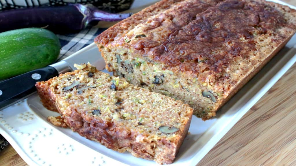 A loaf of sliced eggplant zucchini bread on a white rectangular plate with a eggplant and zucchini in the background.