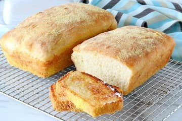 Two Loaves of English muffin bread on a wire cooling rack.