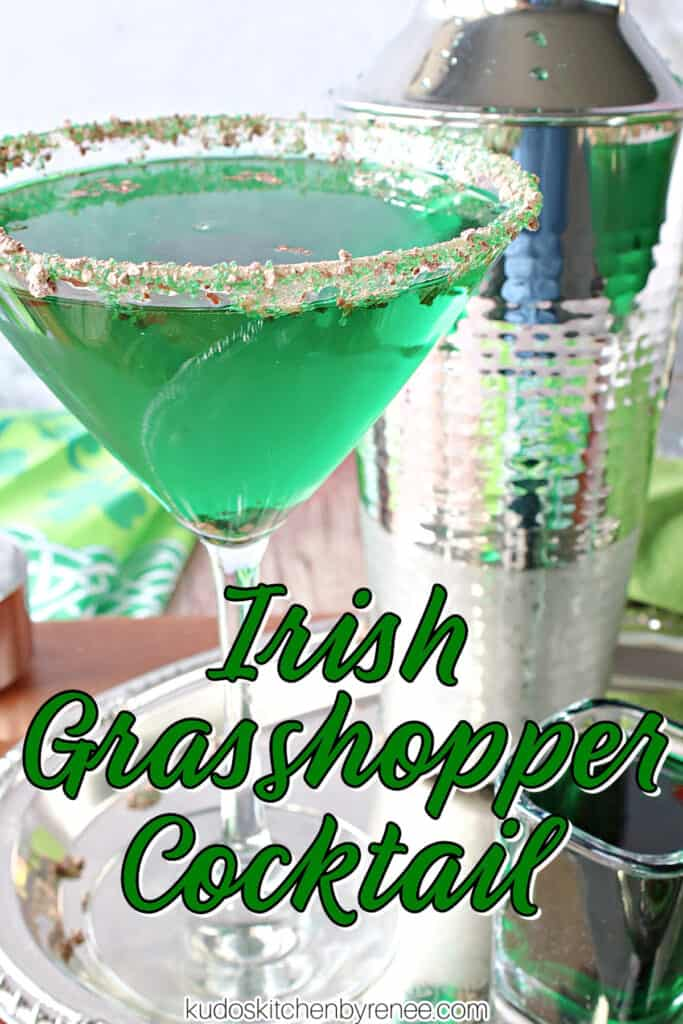 A vertical closeup photo of a martini glass filled with a green Irish Grasshopper Cocktail, and a cocktail shaker on a silver platter along with a title text overlay graphic.