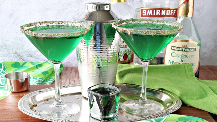 A couple of martini glasses on a silver tray filled with green Irish Grasshopper Cocktails along with a cocktail shaker and a shot glass.