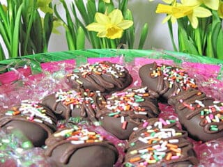 A basket filled with Chocolate Peanut Butter Eggs with daffodils in the background.