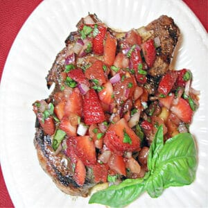 A directly overhead photo of a Pork Chop with Strawberry Relish on a white plate with fresh basil as garnish.