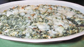 An oval casserole dish filled with Spinach Artichoke Dip topped with cheese.