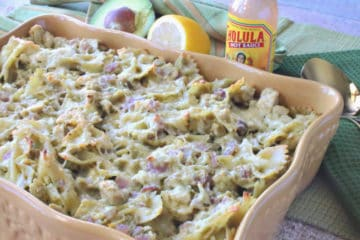 A casserole filled with a chicken artichoke pasta and an avocado and lemon in the background.
