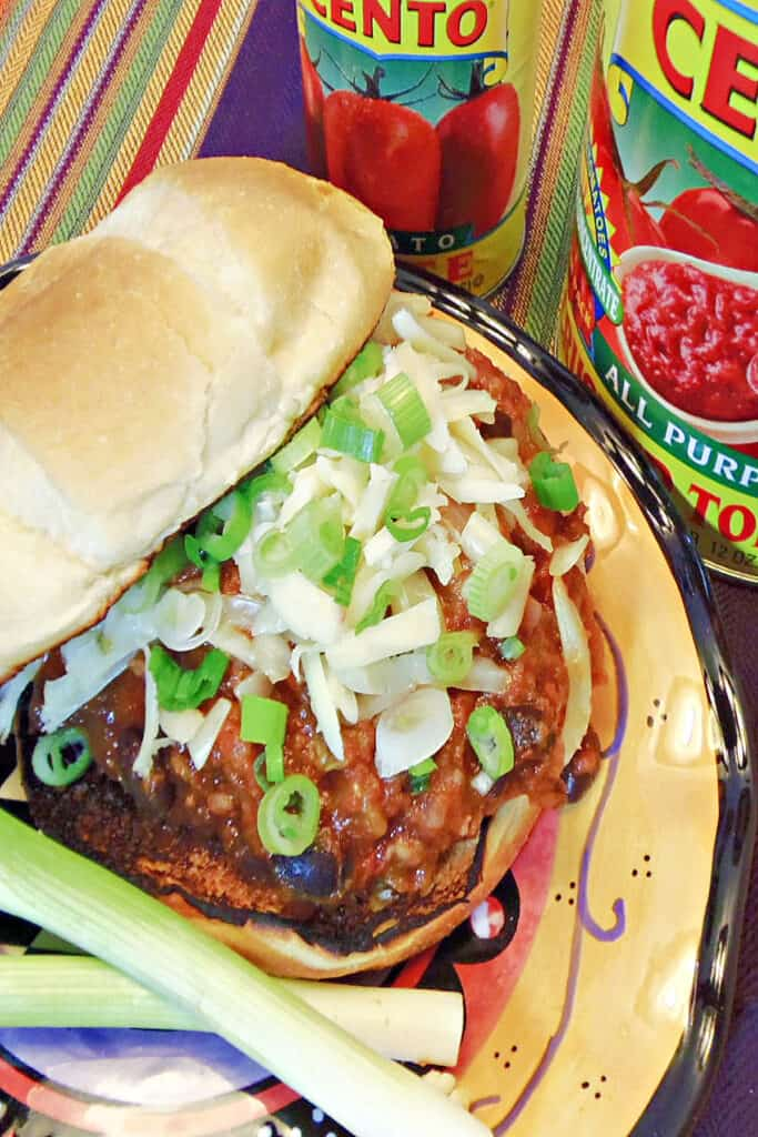 An overhead closeup photo of a Sloppy Jose Pork Sausage Sandwich topped with cheese and scallions along with a toasted bun.