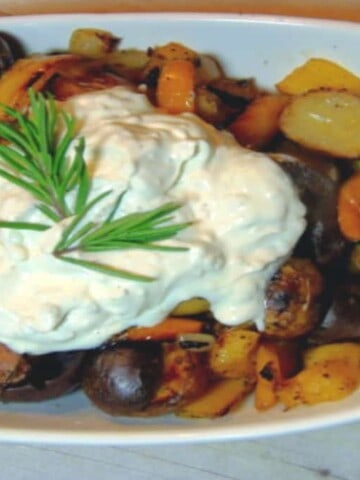 A white oval bowl filled with colorful new potatoes and a large dollop of sour cream and rosemary on top