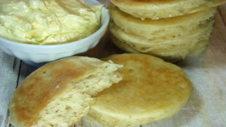 The inside of a homemade crumpet in the foreground and a stack of crumpets with whipped orange honey butter in the background.