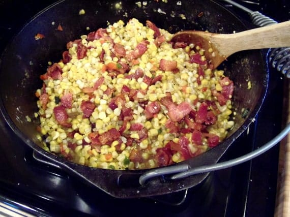 Closeup photo of fried corn with bacon in a cast iron pan.