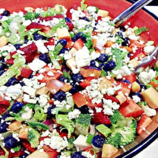 A colorful Summertime Chopped Salad with blueberries, romaine, strawberries, and blue cheese.