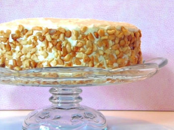 A whole banana poppy seed cake on a glass cake stand covered in chopped macadamia nut cookies