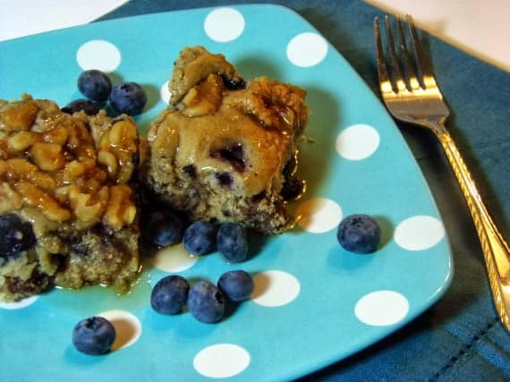 Two slices of sausage blueberry breakfast casserole on a blue and white polka dot plate with fresh blueberries