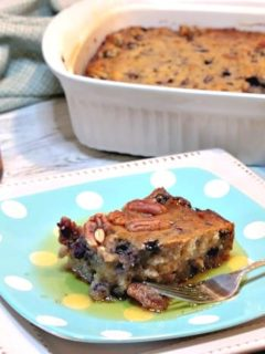 A square of blueberry sausage breakfast casserole on a plate with a bottle of maple syrup in the background.