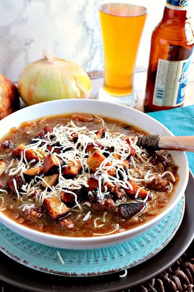 A vertical photo of a white bowl filled with German onion soup, croutons, and cheese. A beer bottle, glass, and onion are in the background.