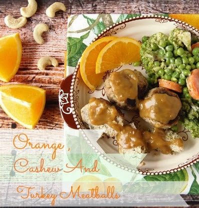 Overhead picture of turkey meatballs on a plate with orange slices and peas.