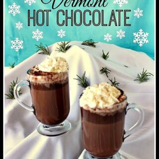 Two cups of hot chocolate on a snow covered mountain.
