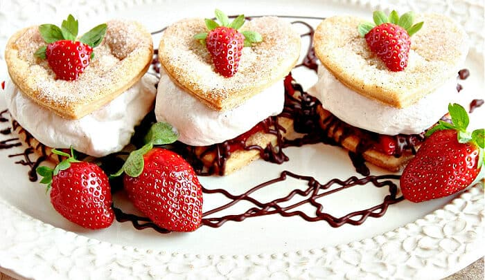 A trio of Deconstructed Strawberry Pies on a white oval platter with a chocolate ganache drizzle and fresh strawberries as garnish.