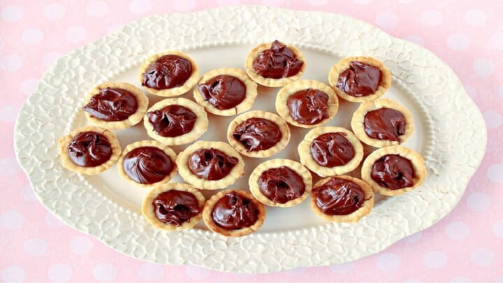 A direct overhead horizontal photo of Nutella Cookie Cups on a pretty white platter with a pink and white polka dot tablecloth.