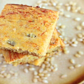 An offset photo of a stack of Buttermilk Green Chile Cornbread on a plate along with corn kernels.