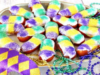A platter filled with Mini Long Johns along with mardi gras beads and a mask.