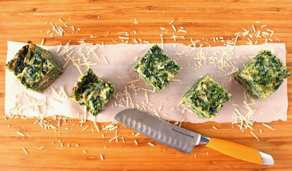 Overhead picture of 5 spinach artichoke crustless quiche squares on a cutting board with a knife.