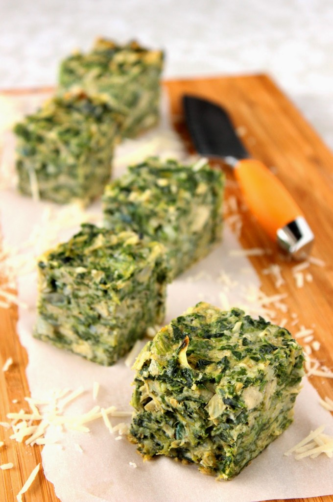 Vertical photo of spinach squares on a cutting board with white parchment paper and a knife.
