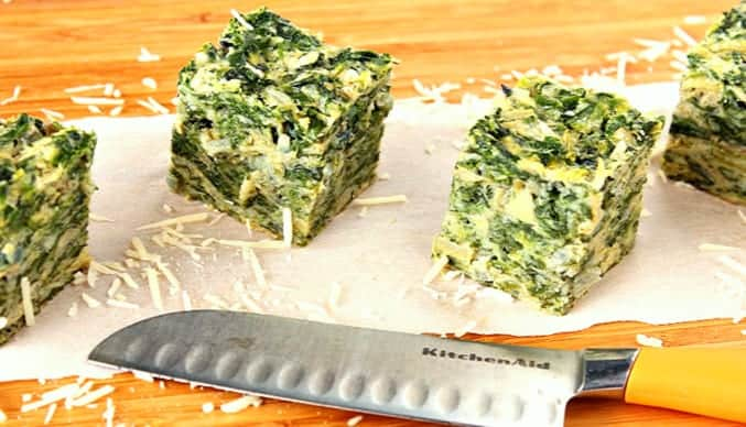 Square of Artichoke and Spinach on a wooden cutting board with shredded Parmesan cheese and a knife.