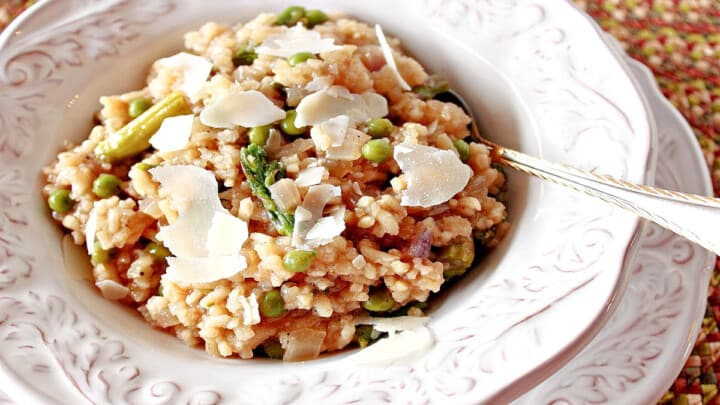 An offset horizontal photo of a pretty white bowl filled with Asparagus and Pea Risotto with Parmesan cheese shavings on top.