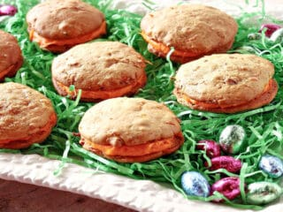 A white platter filled with green Easter grass and Carrot Cake Whoopie Pies.