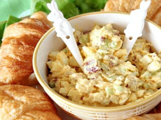 A bowl of Bacon Egg Salad with two bunny spoons surrounded by croissants.