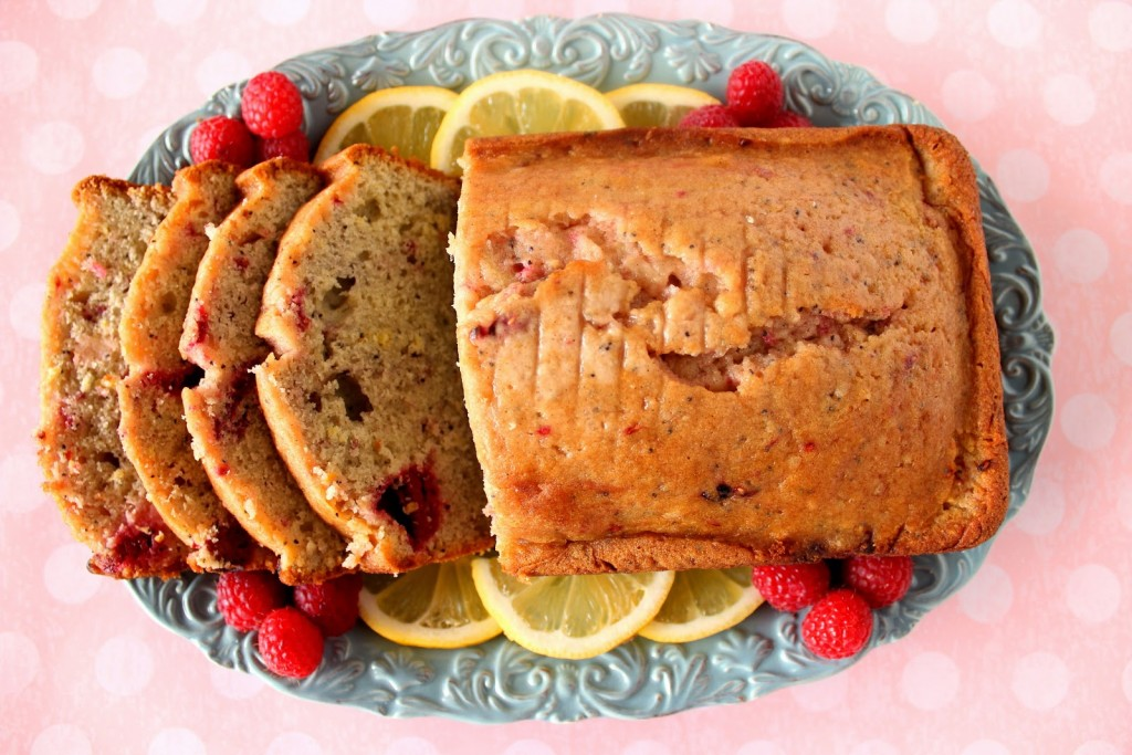 A direct overhead photo of a loaf of sliced lemon raspberry bread on a blue platter with lemon slices and fresh raspberries on the platter.