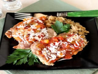 Tropical salsa chicken on a black square plate with a green fork and cilantro