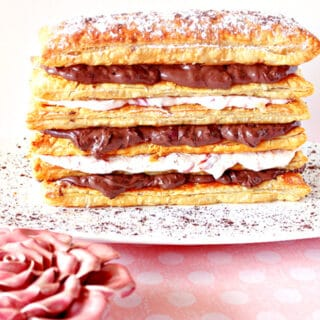 A Chocolate Cherry Pastry Tower on a white plate with a dusting of cocoa powder and a pink rose in the foreground..