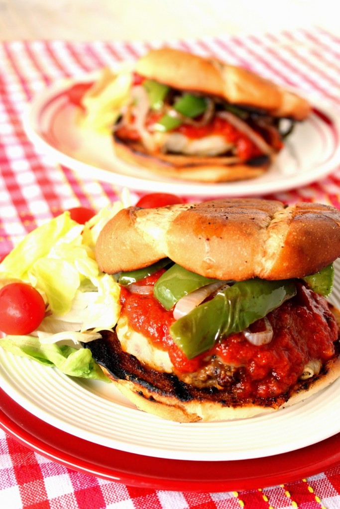 Vertical closeup photo of an Italian sausage pizza burger on a white plate with bell peppers, tomato sauce and a grilled bun.