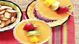 An overhead photo of two Frozen Mango Strawberry Margarita's with salted rims and fresh fruit garnish.