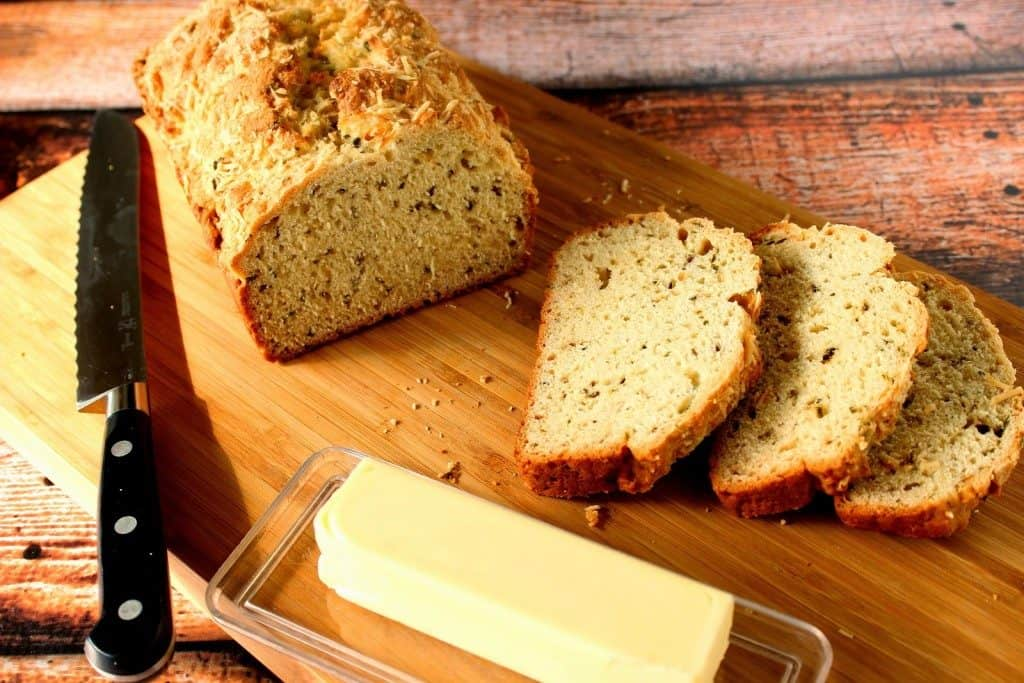 Sliced Homemade Soda Bread on a cutting board with a serrated knife and butter in a dish.