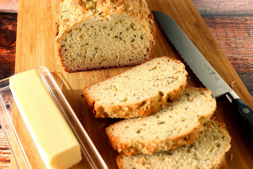 Slices of Homemade Soda bread with herbs and a stick of butter.