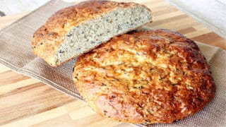 Two rustic loaves of Wild Rice Bread with Onions on a wooden board with a napkin.