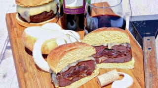 A sliced in half Burger Stuffed with Caramelized Onions on a cutting board along with a glass of wine and some onions.