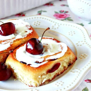 Two Cherry Sweet Rolls on a white plate with fresh cherries on top as garnish.
