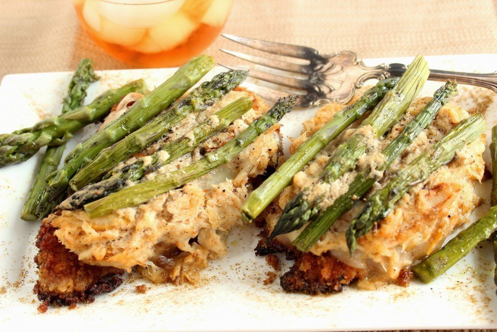 Two chicken Oscar on a plate with crab meat and asparagus topping
