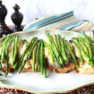 Chicken Oscar on a platter with asparagus spears and a blue and tan striped napkin