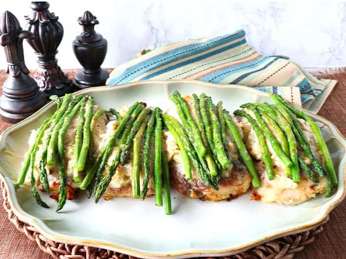 A horizontal photo of Chicken Oscar on a platter with asparagus spears and a blue and tan striped napkin. Valentine's day dinner recipe roundup.