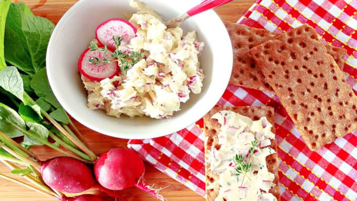 A horizontal photo of a small bowl of Compound Radish Butter with Thyme along with fresh radishes and a red and white checked napkin.