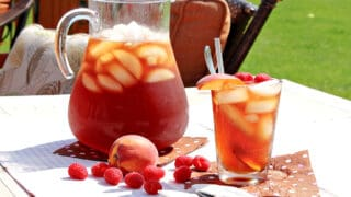 A pitcher and glass filled with ice and Peach and Raspberry Sun Tea.
