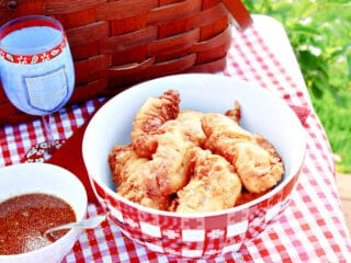 A red and white checked bowl filled with Waffle Batter Fried Chicken Tenders along with a picnic basket.