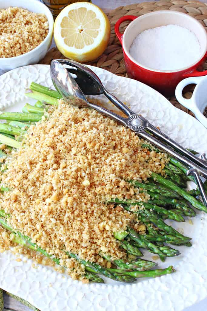 A overhead vertical closeup photo of Asparagus with Breadcrumbs on a pretty white platter with serving tongs.