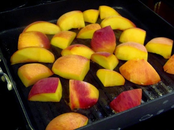 Grilling peach slices in a grill pan.